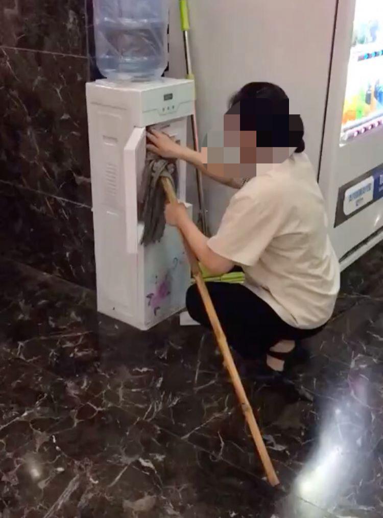 保洁员用拖把擦饮水机。 视频截图