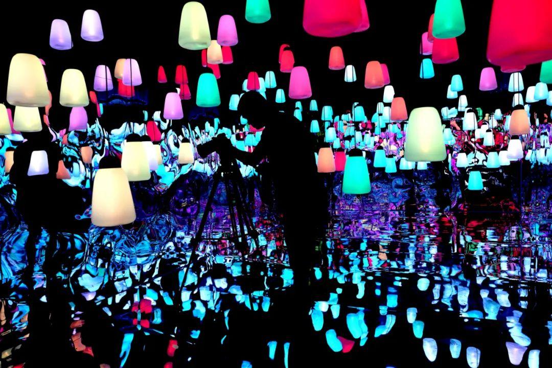 6月19日晚,一名摄影者在上海青衫夜市的灯光全息互动展上拍摄