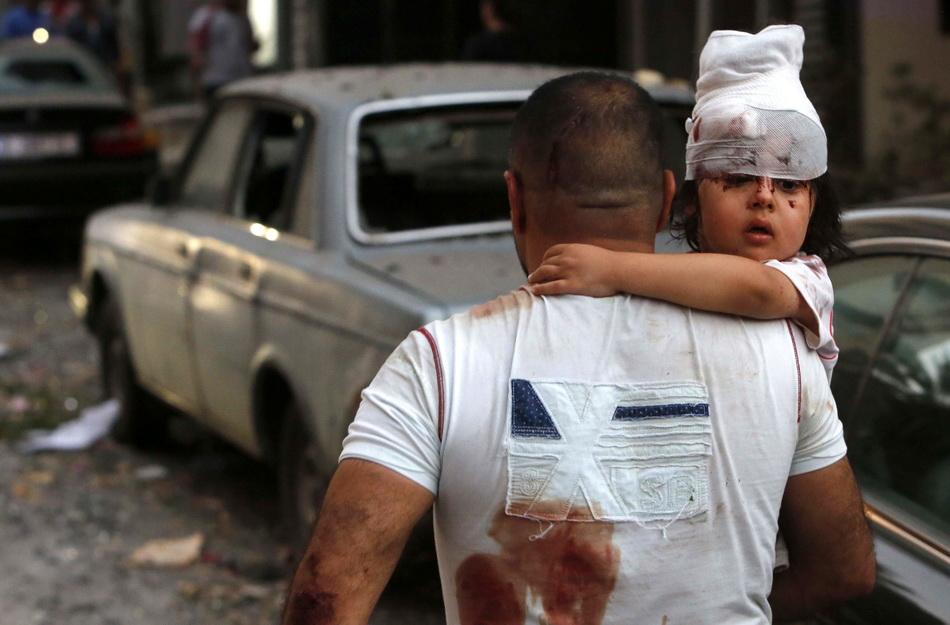 一名男子穿梭在废墟中,怀中的女童满脸惊恐。