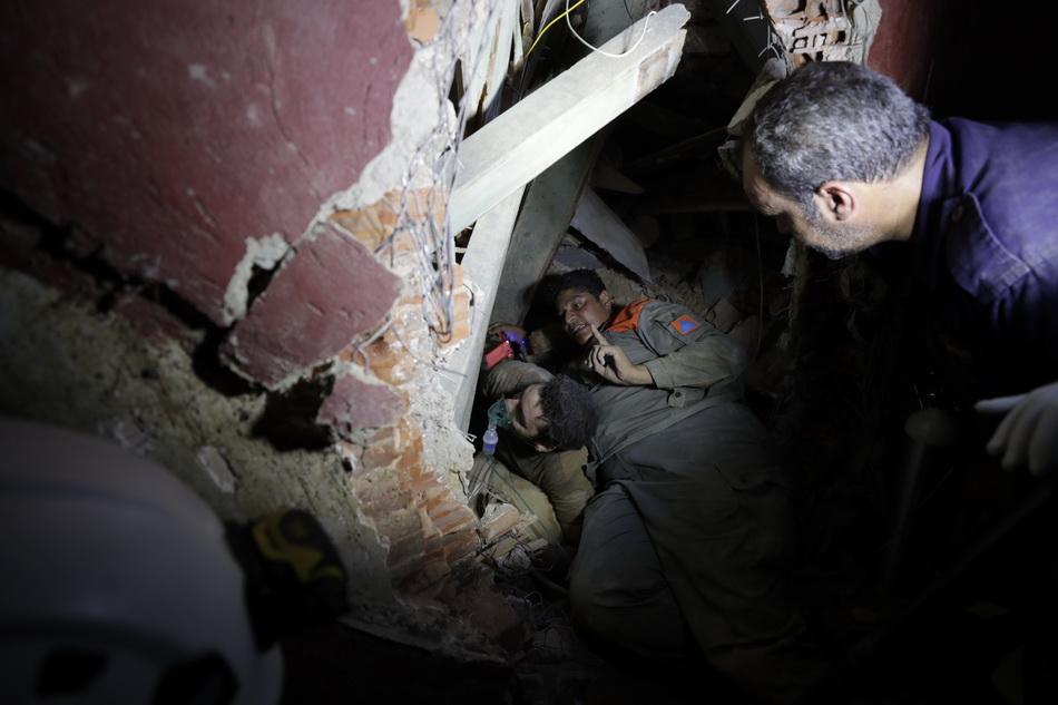 贝鲁特士兵在废墟中搜救到一名幸存者,并给伤者提供氧气,想办法进行下一步救援。