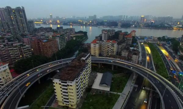 """2015年,广州洲头咀隧道通车,一栋被高架桥包围的""""圈中楼""""走红网络,是广州有名的""""钉子户""""。南方都市报 图"""