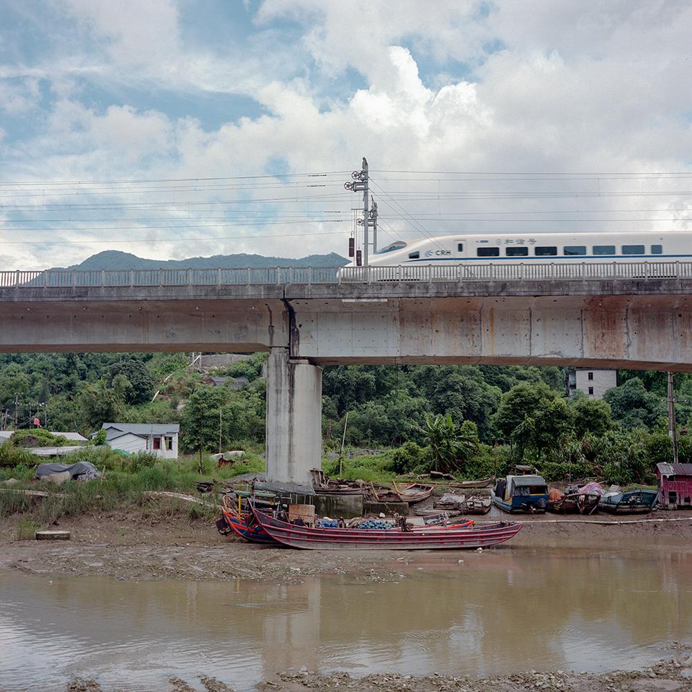 2019年8月,飞鸾镇,河道上破旧的渔船和上方呼啸而过的高铁。