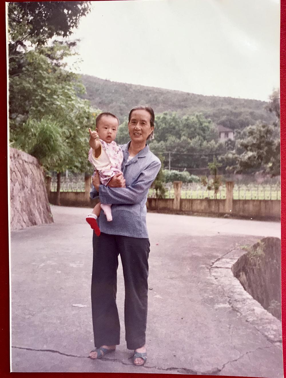 1991年,飞鸾镇,基地里外婆抱着刚满一周岁的我。