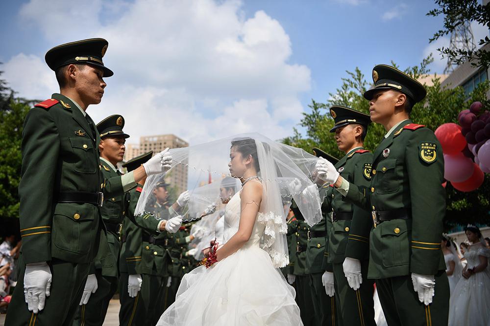 8月6日,礼兵为新娘们盖上头纱。当日,武警云南省总队昆明支队26对新人举办集体婚礼,在家人的祝福和战友的见证下,步入婚姻的殿堂。刘冉阳 /中新社 图