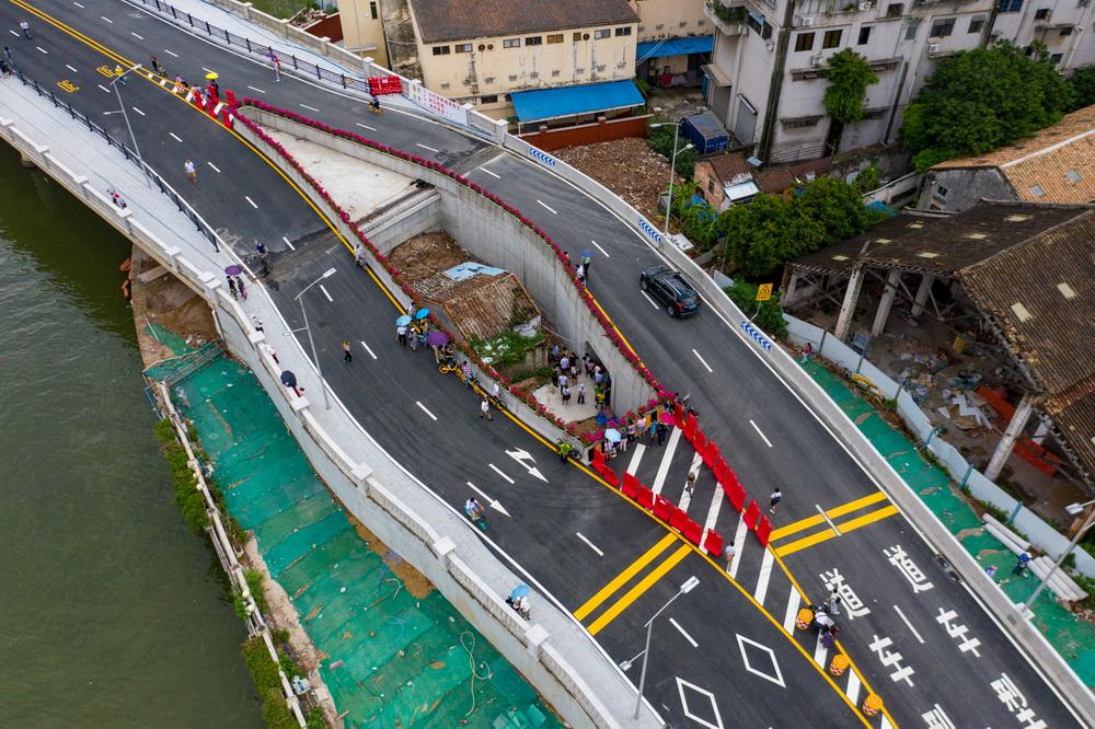 """近日,广州市环岛路海珠涌大桥中央的""""钉子户""""火了。海珠涌大桥于8月3日正式建成开通。市民发现桥中间有一个小小的凹陷处,一处民房被双向车道环形包围。这所""""嵌在""""大桥中央的房子,被网友戏称为""""海珠之眼"""",有市民专门前来参观。汤文健/人民视觉"""