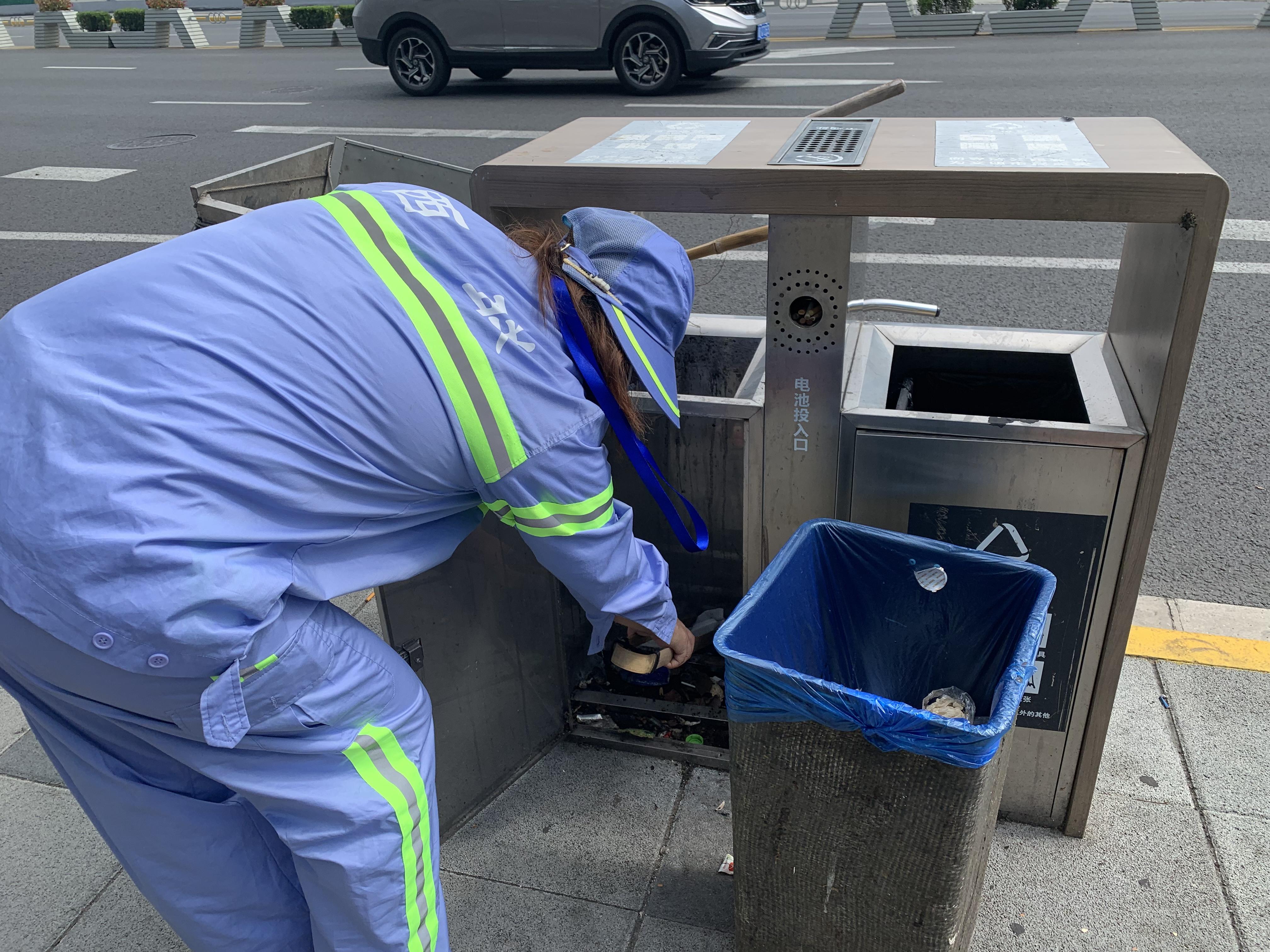 环卫工人张玉梅将路边垃圾桶内的垃圾全部捡拾出来。澎湃新闻记者栾晓娜摄
