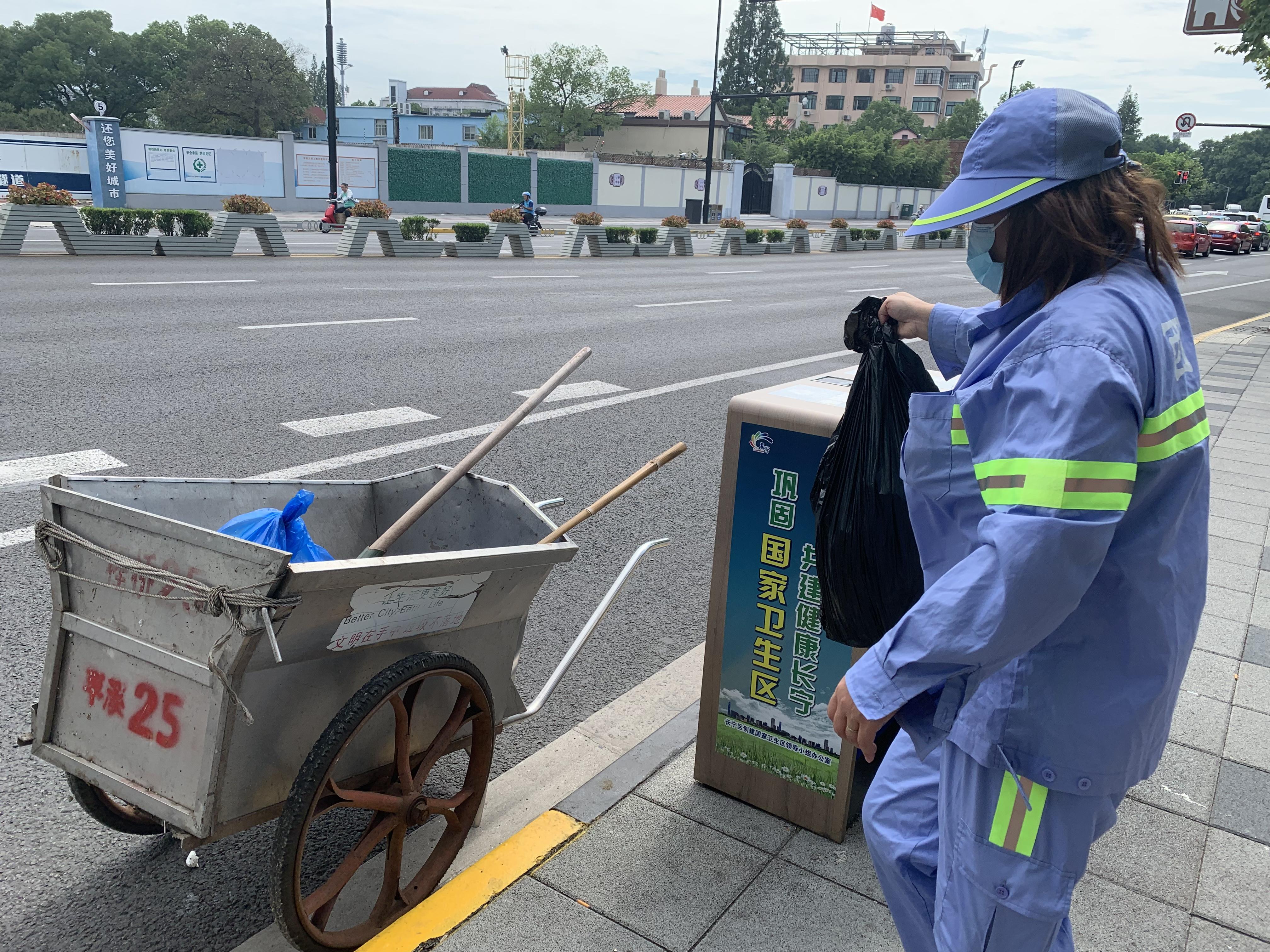 环卫工人张玉梅将路边垃圾桶内的垃圾全部清运到小推车里。澎湃新闻记者栾晓娜摄