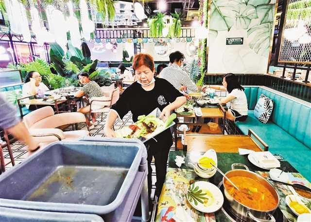 8月11日,江北区石马河龙湖源著天街,某海鲜火锅店,服务员将顾客剩下的菜品倒掉。
