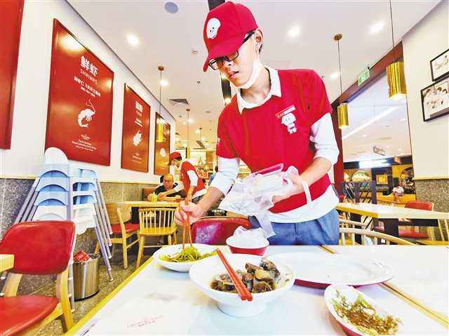 8月11日,江北区石马河龙湖源著天街某水饺店,服务员为顾客将剩余的菜品打包。图片由首席记者崔力摄 视觉重庆