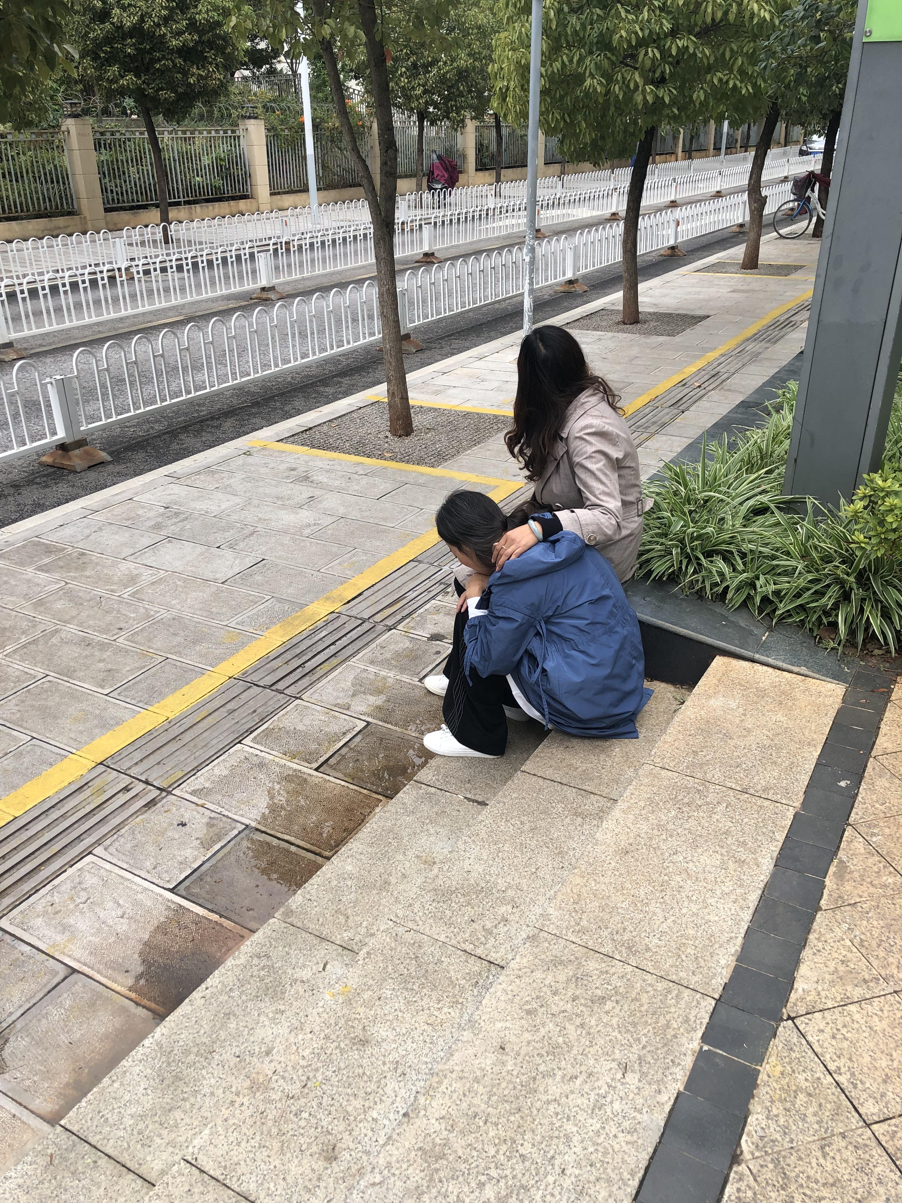 从酒店去警局的路上,陈美莲坐在台阶上,陷入悲伤