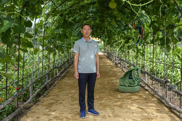 """2020年8月,内蒙古兴安盟义勒力特嘎查,义勒力特嘎查党支部书记白双龙站在""""开心果园""""的葫芦藤下。"""