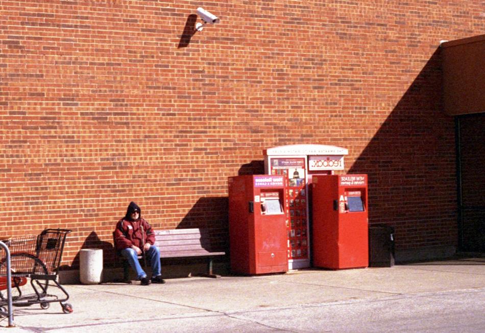 坐在超市红砖表墙旁的漂泊者。听以前自愿过的慈善机构说芝添哥市的漂泊者救治中央(walk-in shelters)由于人群起伏性大以及空间拥挤等因为一度成为了新冠高发场所。