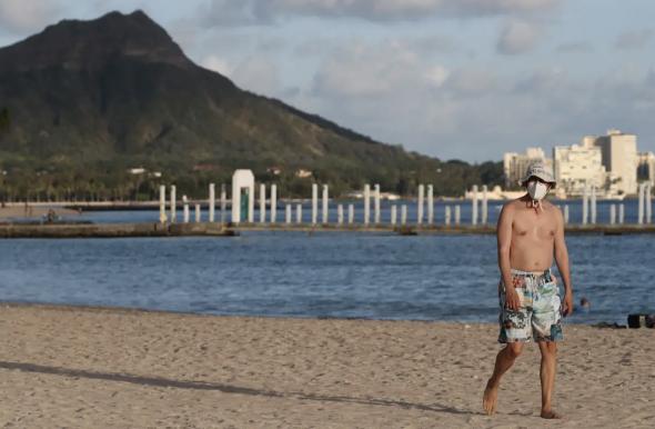 △一名游客戴着口罩在夏威夷威基基海滩散步。 图片来源:路透社