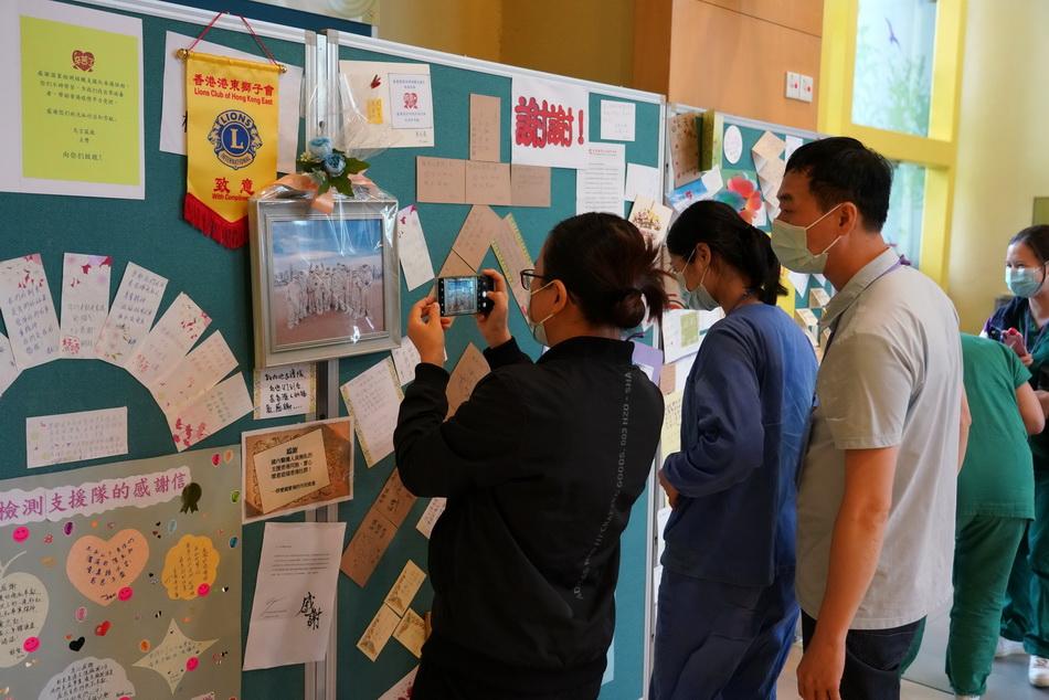 9月12日,内地支援队员在临时休息区观看香港市民送来的心意卡。支援队平时开会的会议室里,一面墙上贴满了香港市民送给支援队的感谢信、心意卡、画作等物件。