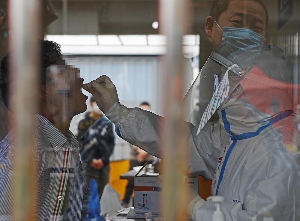 2020年4月14日,一名员工在上海市普陀区第二集中隔离观察点的广场上接受核酸检测。殷立勤/中新社/人民视觉 资料图