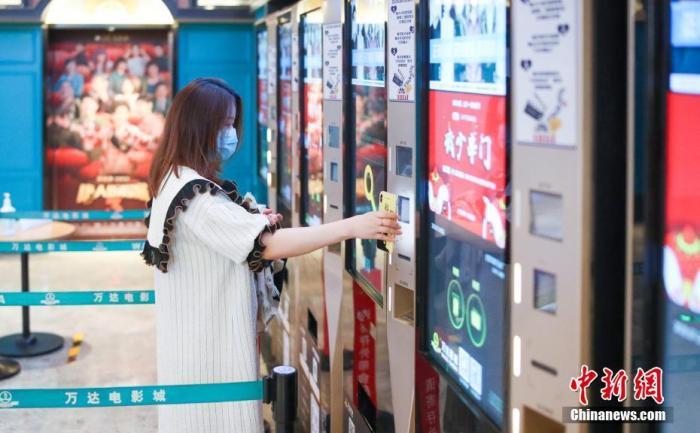 资料图:7月24日,观众在北京万达影城CBD店内自助扫码取票。中新网 图