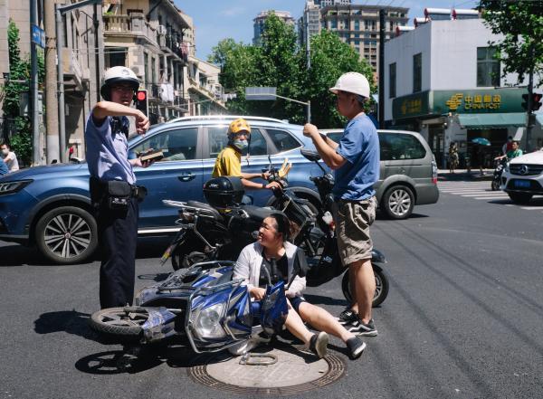 上海市中心十字路口,外卖骑手经过被助动车撞倒的走人。澎湃讯息记者 周平浪 图