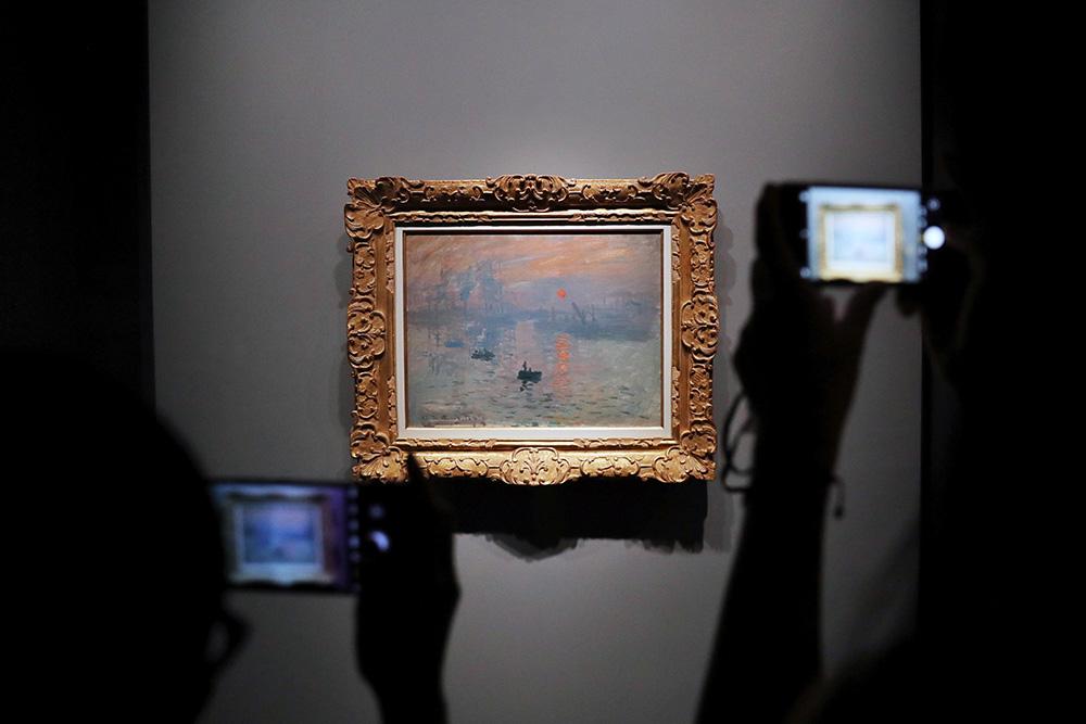 """9月20日,观众隔着玻璃欣赏莫奈画作《日出·印象》。当日是周日,一早就有民众在外滩中山东一路1号艺术博物馆排起长队。近日,展览""""日出·光明——莫奈《日出·印象》""""特展在上海开幕。这是150年来,印象派画家莫奈的代表作《日出·印象》油画原作首次登陆中国。据悉,此次展览以《日出·印象》为主题,共展出47件印象派和当代作品,其中包括法国巴黎马摩丹莫奈博物馆镇馆之宝《日出·印象》等9件莫奈画作。张亨伟/中新社 图"""