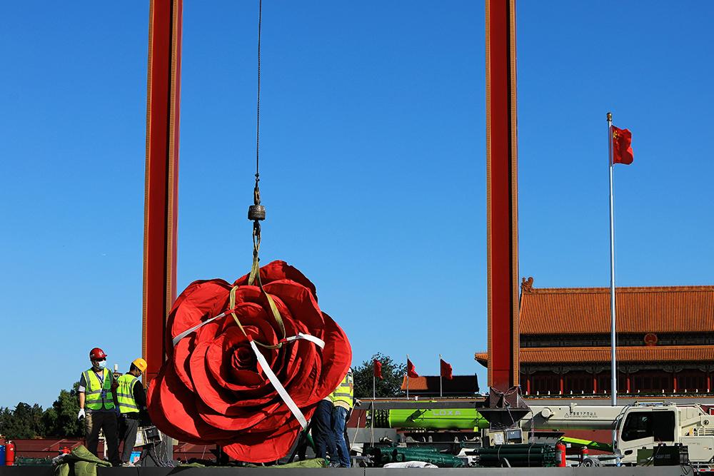 """9月17日,工人们在天安门广场中心布置""""祝福祖国""""巨型花篮,预计25日左右完工亮相,与市民共庆国庆。花坛顶高18米,以喜庆的花果篮为主景,花篮为钢架结构,篮身为玻璃钢材质,可抗10级风。陈燕华/人民视觉 图"""