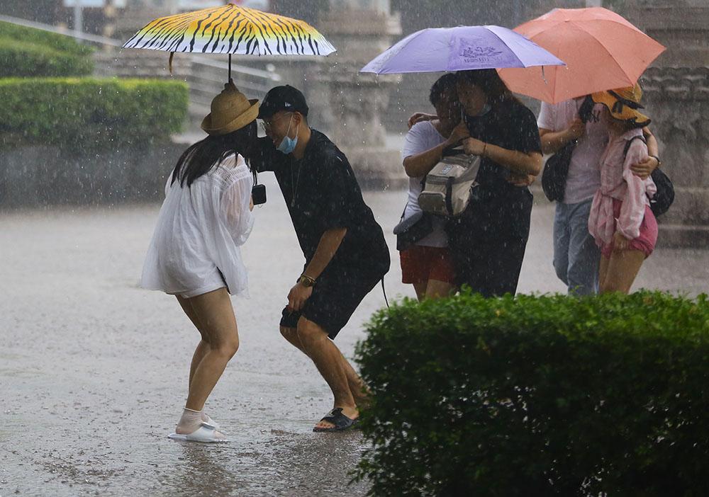 """9月17日,三亚一景区内,游客们俩俩挤在伞下躲雨。当日,受今年第11号台风""""红霞""""影响和弱冷空气共同影响,海南陆地迎来明显降雨。人民视觉 图"""