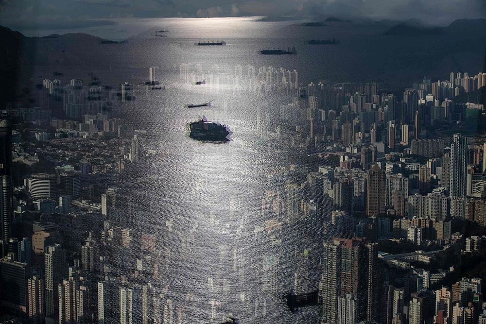 9月20日,中国香港,人们在观景台上俯瞰城市景观,窗户上映出来往船只的影像。MAY JAMES /人民视觉 图