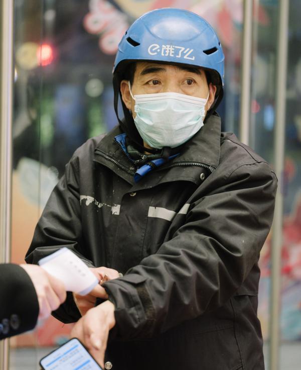 2020年情人节当天,在上海某园区外被检测体温的外卖骑手。澎湃新闻记者 周平浪 图