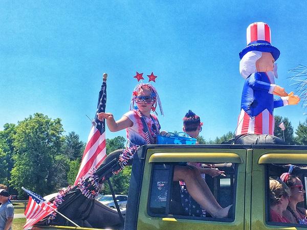 """2018年7月 4日,纽约州杰镇居民自发的独立日游行,是很受欢迎的民间狂欢会,车顶上的小孩在向路人抛撒糖果。人们用美国国旗星条旗上的红蓝白三个颜色做出创意无限的装饰来。有意味的是,我发现这些星条旗、头箍、彩带、T恤、太阳镜和充气娃娃,全部标记着""""中国制造""""。"""