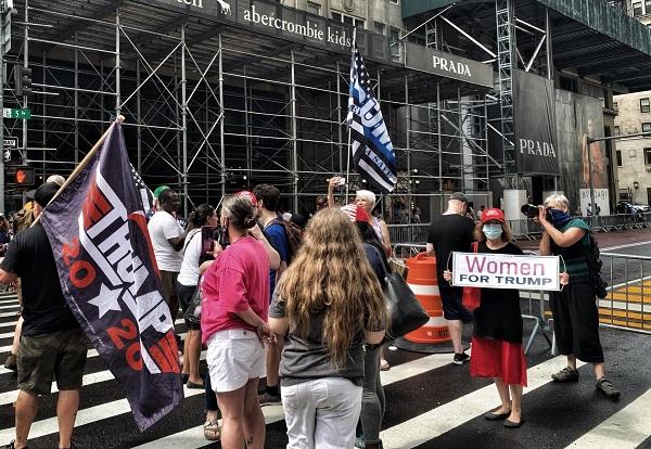 """2020年7月11日,纽约曼哈顿第五大道川普大厦前支持川普、抗议""""黑命贵""""的人群。路障后面黄色的字迹就是市长白思豪带人刷下的三个英文单词""""黑命贵(Black Lives Matter)""""。图右女性手持的横幅上写着""""特朗普妇女后援团""""字样。"""