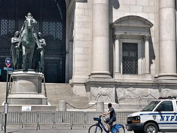 """2020年7月23日,美国自然历史博物馆门前的罗斯福塑像。始终有2名警察全天候轮值,以防发生与之相关的暴力冲突。塑像前方是博物馆新近放置的说明:""""为纪念前纽约政府和美国总统罗斯福,本雕塑于1940年向公众揭幕。如今,有人将其视作一支英勇的团队,有人将其视作种族分级的符号。"""""""