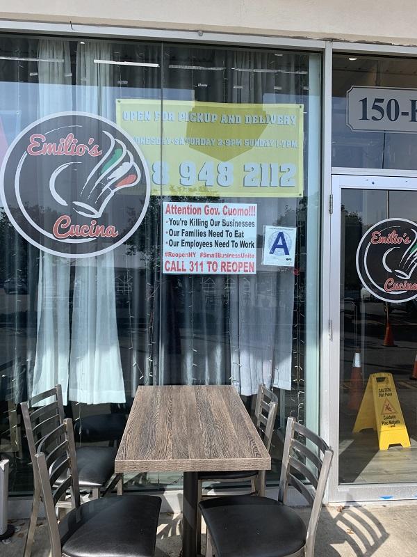 """2020年7月15日,纽约一家供应意大利简餐的小吃店门上的告示。上书:""""科莫州长,注意了:你在扼杀我们的生意,我们的家庭需要吃饭,我们的员工需要工作!""""该店主希望大家拨打311纽约市民热线,呼吁复市。署名是两个组织:""""纽约复市""""和""""小业主协会""""。"""