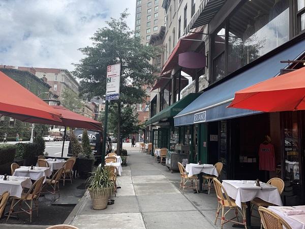 """2020年8月7日,由于纽约市依旧禁止室内餐饮,曼哈顿上东区麦迪逊大道上的""""岛屿饭店""""只能将餐桌放到马路上,部分餐桌甚至放到了邻近的杂货店、服装店和书店的门外。"""