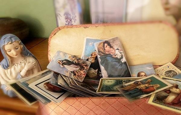 """2020年9月10日晚间,海伦的祷文卡(prayer card,正中,""""圣母与圣婴"""")放到了她卧室的锦盒里,后面是她丈夫托尼的祷文卡,右上背景是年轻时候的海伦。纽约的天主教徒和基督教徒在葬礼后会分发祷文卡给亲友,正面一般为宗教图像,反面有亡者的生卒年月和祝祷词。海伦把她收到的祷文卡都珍藏在这个锦盒里,这里有伴随了她一生的友情、亲情和爱情。"""
