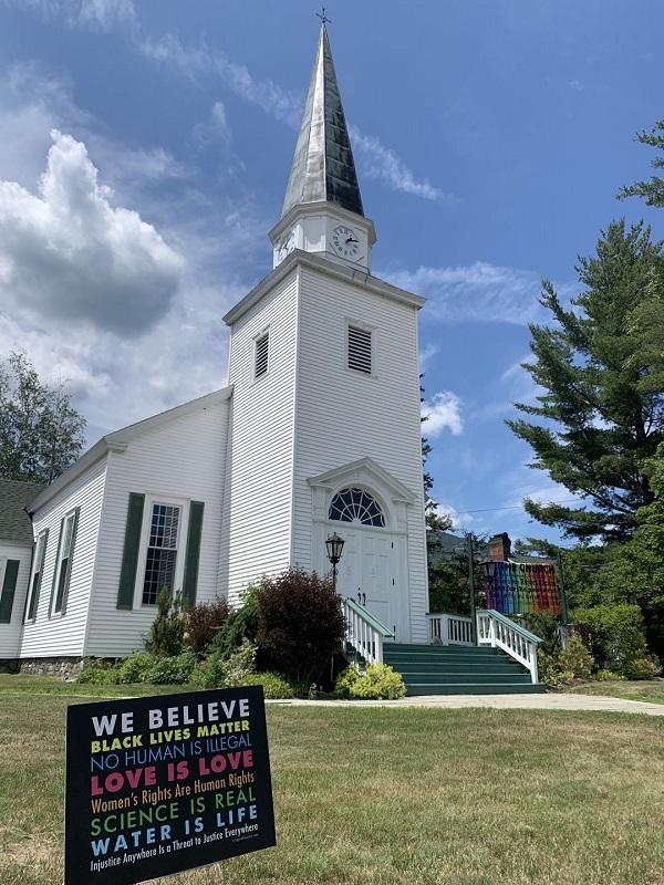 """2020年8月16日,纽约州基恩镇上的基督教堂。这个地区的教民大多是支持民主党的较富裕阶层,这类教堂一般都继续延迟开放。教堂门口悬挂着支持同性恋的旗帜,草地上的标志牌上写着:""""我们相信:黑命攸关、没有人是非法的,爱就是爱,女权就是人权,科学是真的,水是生命,任何地区的不公正就是对所有地区公正的威胁。""""和平圣母堂在堕胎、同性恋和移民等议题上持保守态度,而这个教堂则代表着与之相反的另一类。两类教堂在教民的阶层、收入、族裔、来源地和政治态度等方面都有明显差异。"""