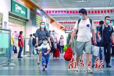 10月7日,长假进入尾声,深圳火车站返程客流持续攀升。图为旅客佩戴口罩携带行李有序出站。南方日报记者朱洪波 图