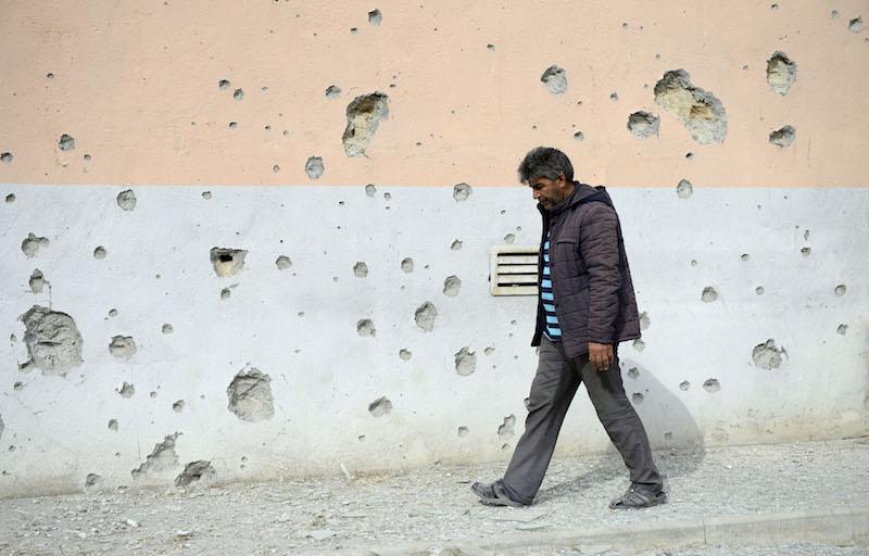 亚美尼亚与阿塞拜疆在纳卡地区爆发新一轮冲突,别名村民从布满弹孔的墙壁旁经过。