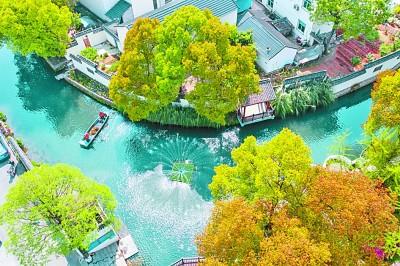 浙江省长兴县龙山街道渚山村的保洁人员乘船清理河面漂浮物。新华社发