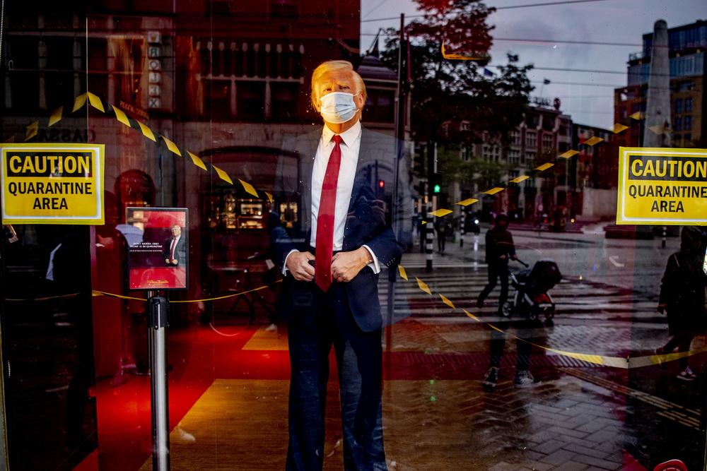 """当地时间10月3日,荷兰阿姆斯特丹杜莎夫人蜡像馆内,戴着口罩的美国总统特朗普蜡像在""""隔离""""区内。"""