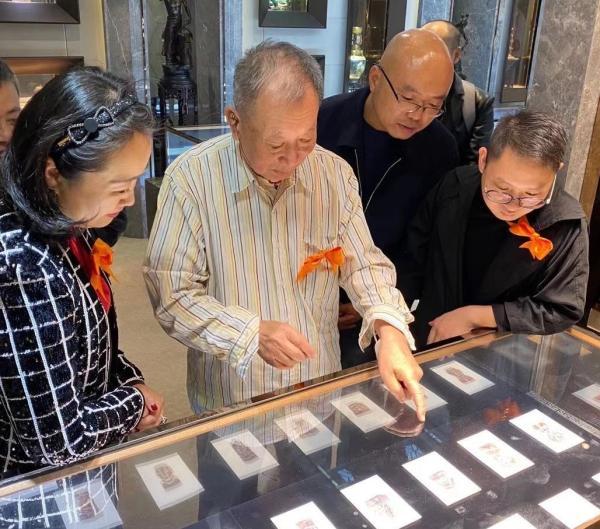 90岁的丁立人(中)在展览现场介绍文献