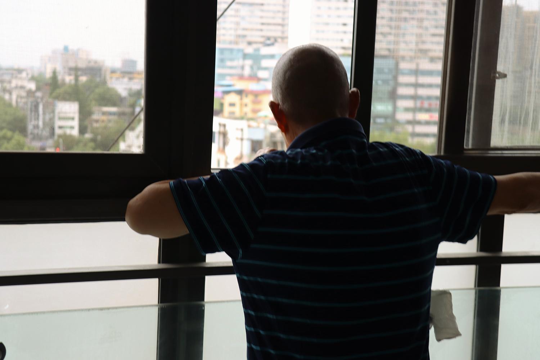 从厨房出来,爷爷就趴在阳台窗口,这是他闲来的民风之一。