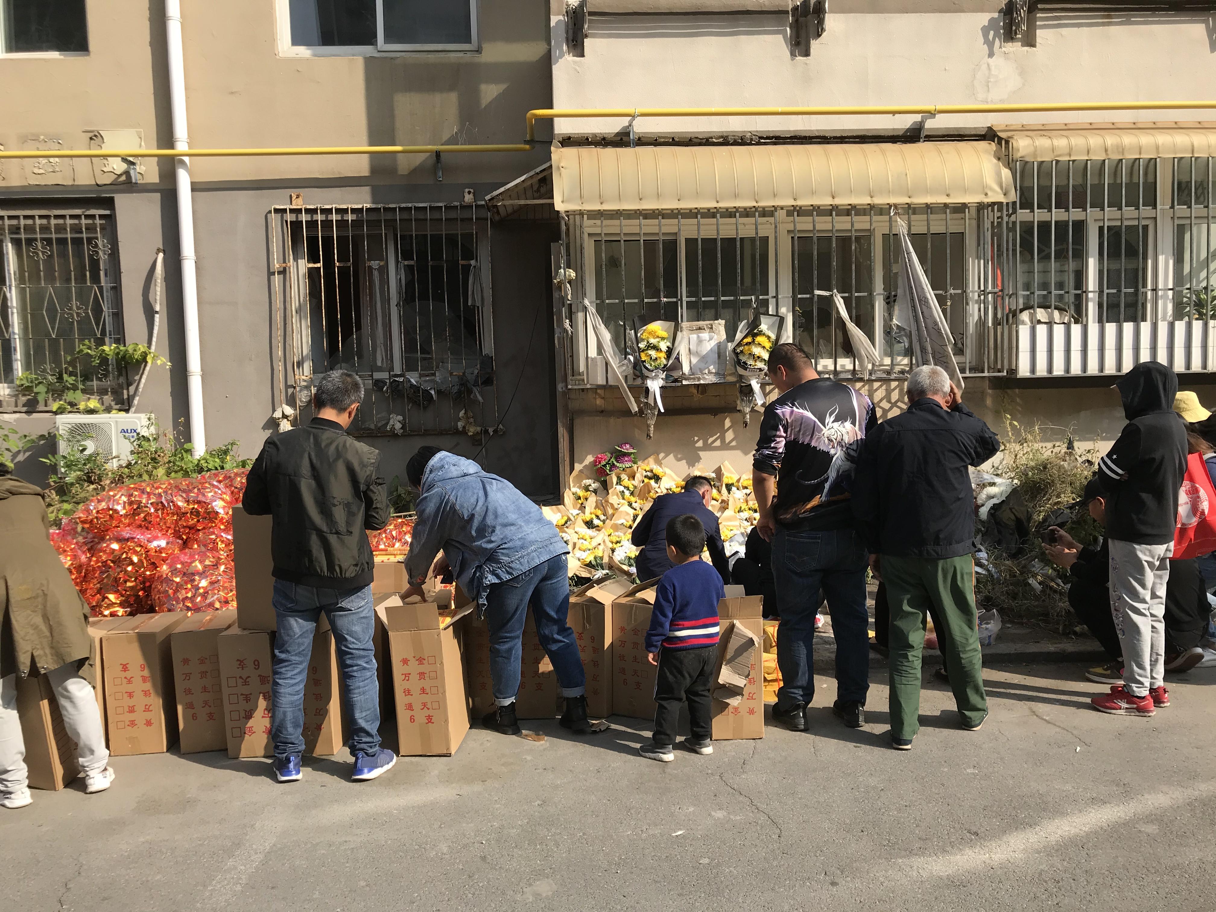 事发现场凶手蔡某某的家门前,现场堆满了前来吊唁的人送来的黄白色鲜花和贡品纸钱。