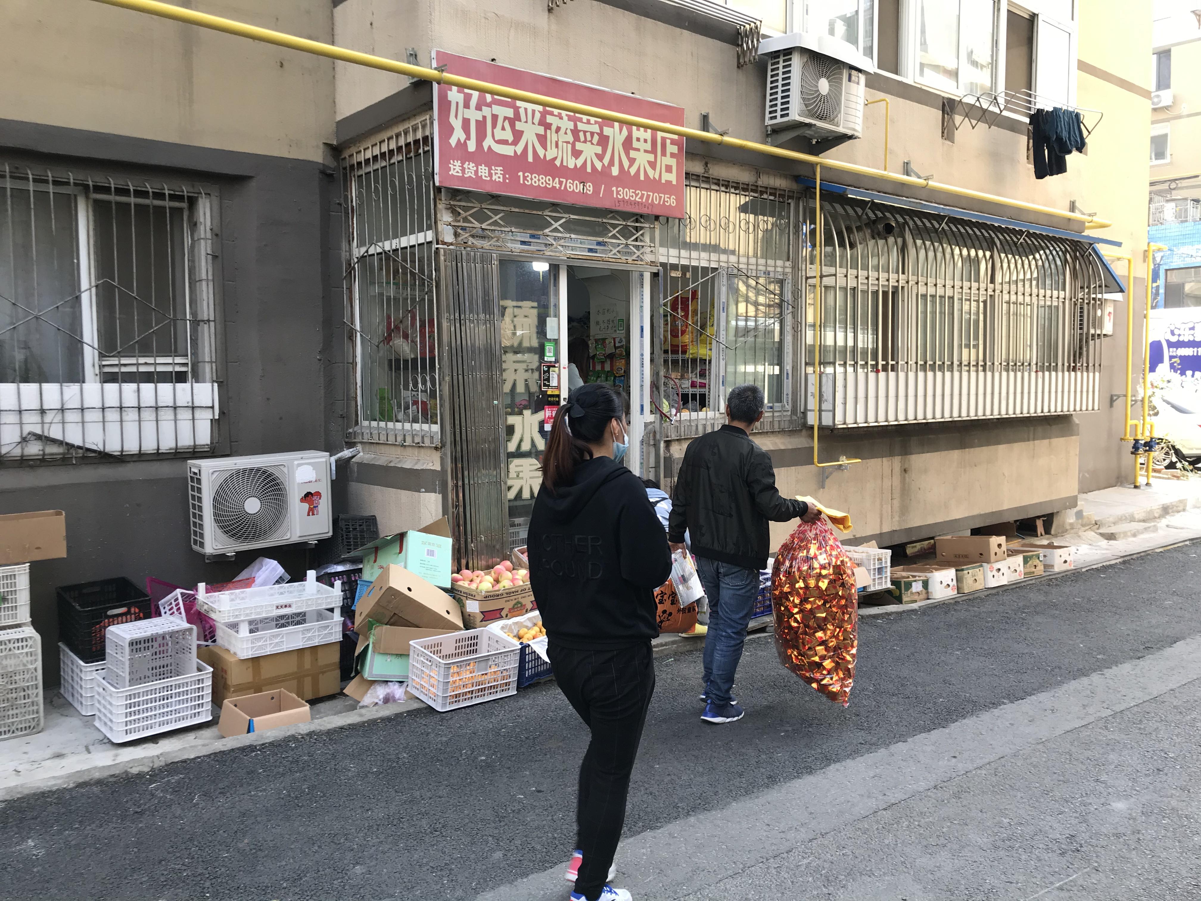 """贺美玲及家人路过自家经营的""""好运来蔬菜水果店"""",案发一个月后,水果店转给了弟弟经营。"""