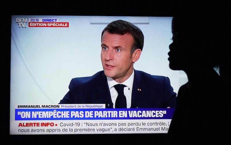 10月14日,观众在法国巴黎家中收看法国总统马克龙接受采访的电视节目。 法国总统马克龙14日晚宣布,将从17日起在法兰西岛大区(大巴黎地区)和其他8个大城市实施宵禁,以遏制新冠疫情。