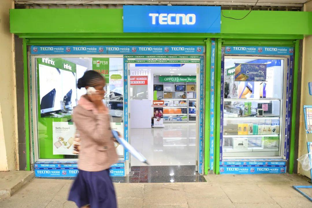 2017年5月9日,在肯尼亚首都内罗毕市中心,一名女子从一家手机经销店前走过。新华社记者孙瑞博摄