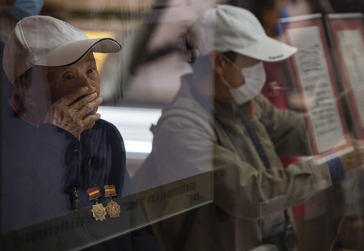 """10月25日,来自四川的老兵魏爷爷在位于北京的中国人民革命军事博物馆参观""""铭记伟大胜利 捍卫和平正义——纪念中国人民志愿军抗美援朝出国作战70周年主题展览""""。此次展览中,有1900余件文物及展品亮相回顾了抗美援朝这段光辉历史,其中824件文物系首次展出。当天起,该主题展览向公众开放,展出至2021年2月底结束。侯宇(摄影部)/中新社"""