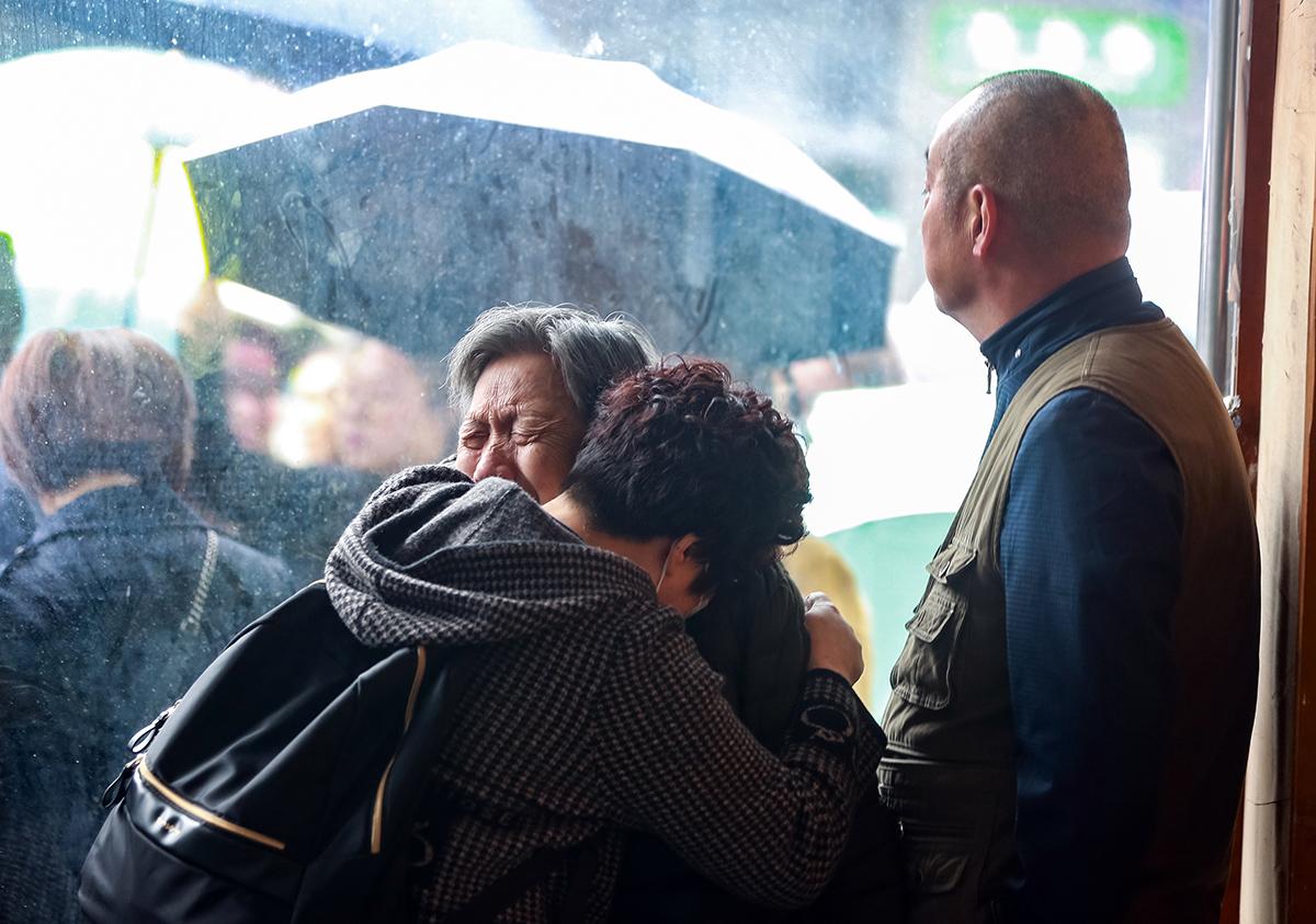 """10月15日,在四川省广元市苍溪县,当载着李雨阗灵柩的灵车经过时,他的外婆(前左)失声痛哭。当日,苍溪县各界群众自发走上街头,送别勇救坠江女子因公牺牲的31岁民警李雨阗。广元市公安局党委决定,将李雨阗生前使用的""""035225""""警号作为特殊警号永久封存。10月19日上午,李雨阗同志先进事迹宣讲报告团在苍溪中学校学术报告厅展开首场宣讲。 新华社 图"""