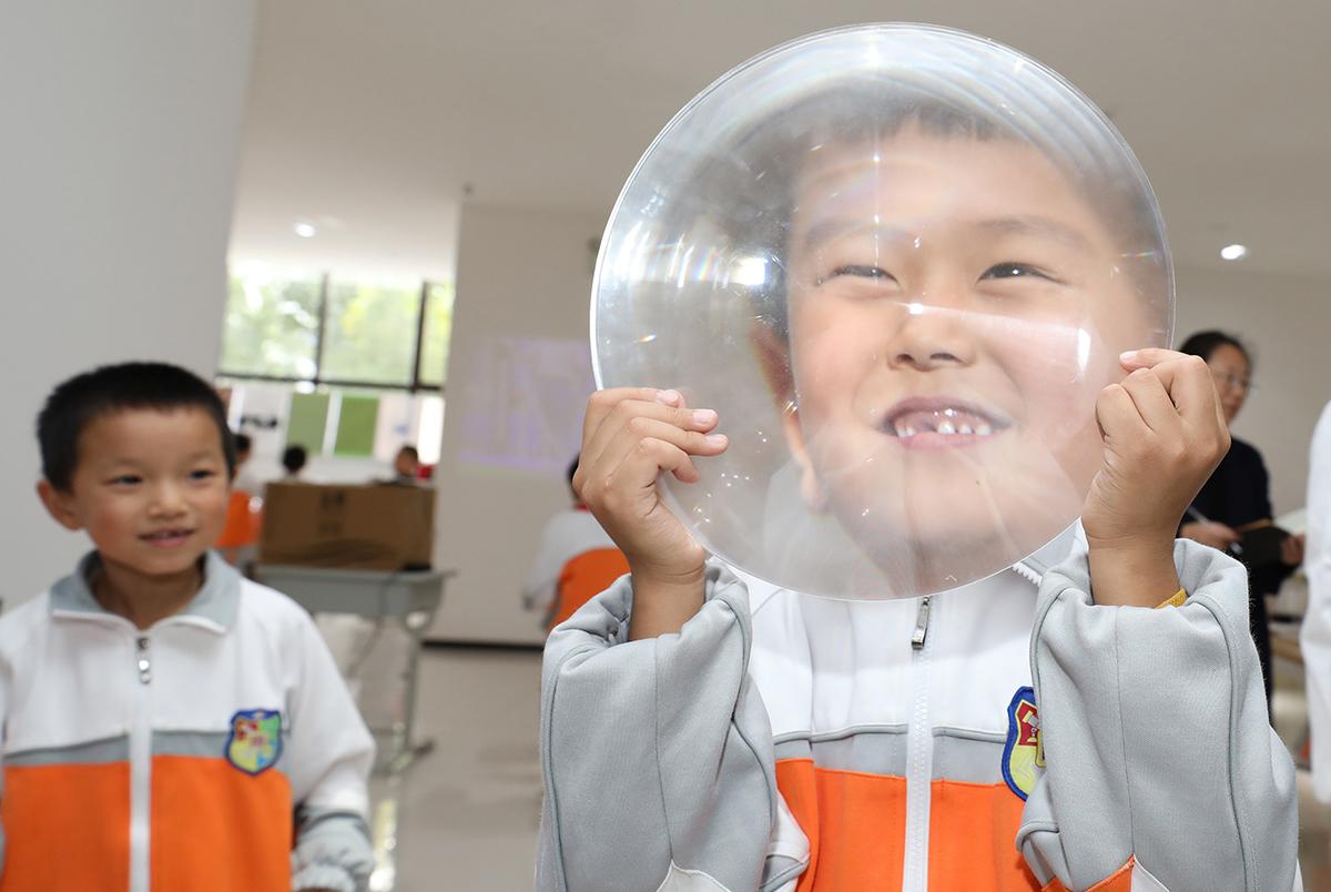 10月20日,西安国际港务区陕西师范大学陆港小学,小朋友体验放大镜的神奇。科技互动展览现场近百个科学小实验和科普项目,紧紧抓住了学校师生们的眼球。减影/IC 图