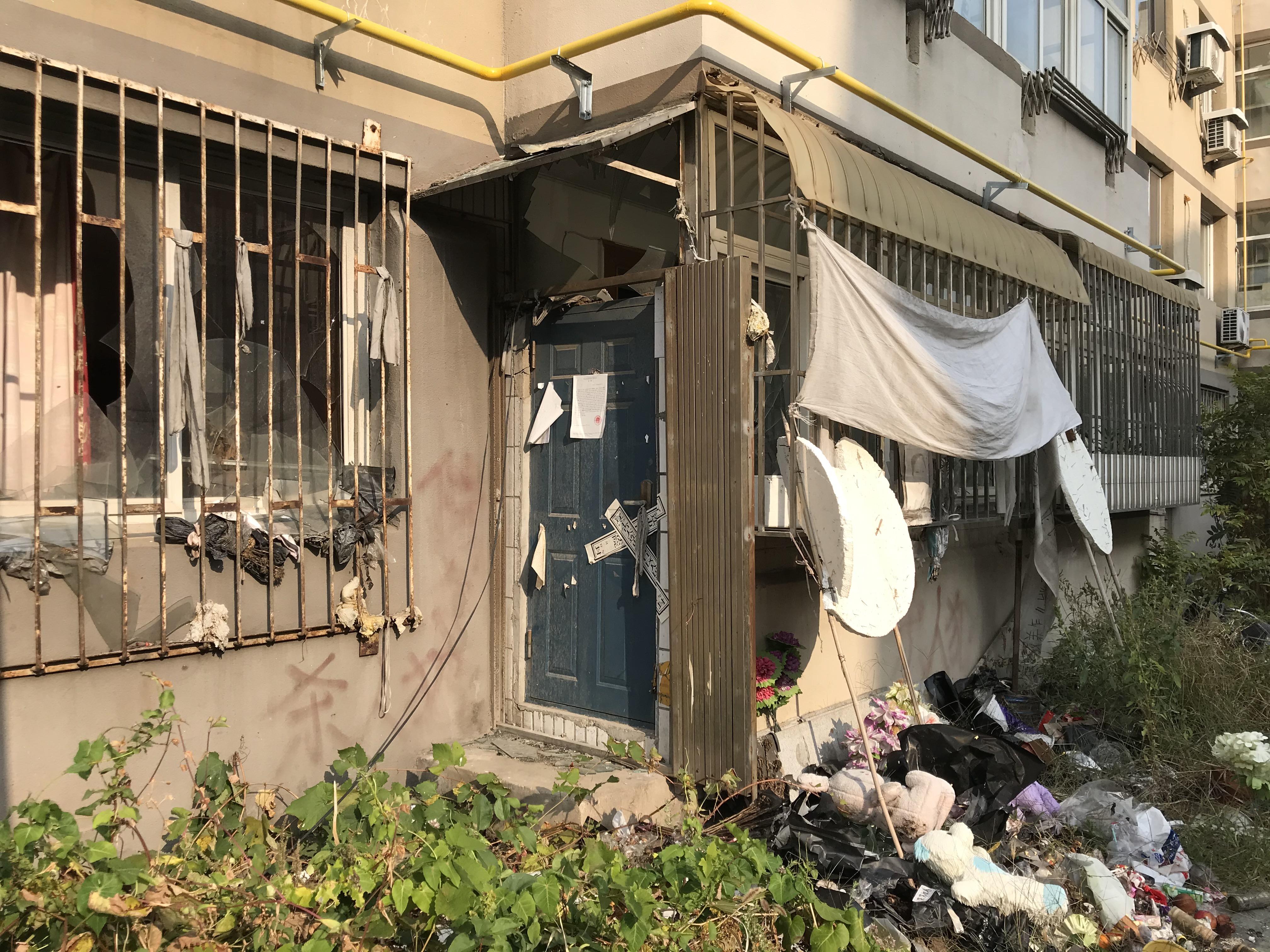蔡鸣的家,门前放着花束、腐烂的水果、灰扑扑的玩偶。澎湃新闻记者 沈文迪 图
