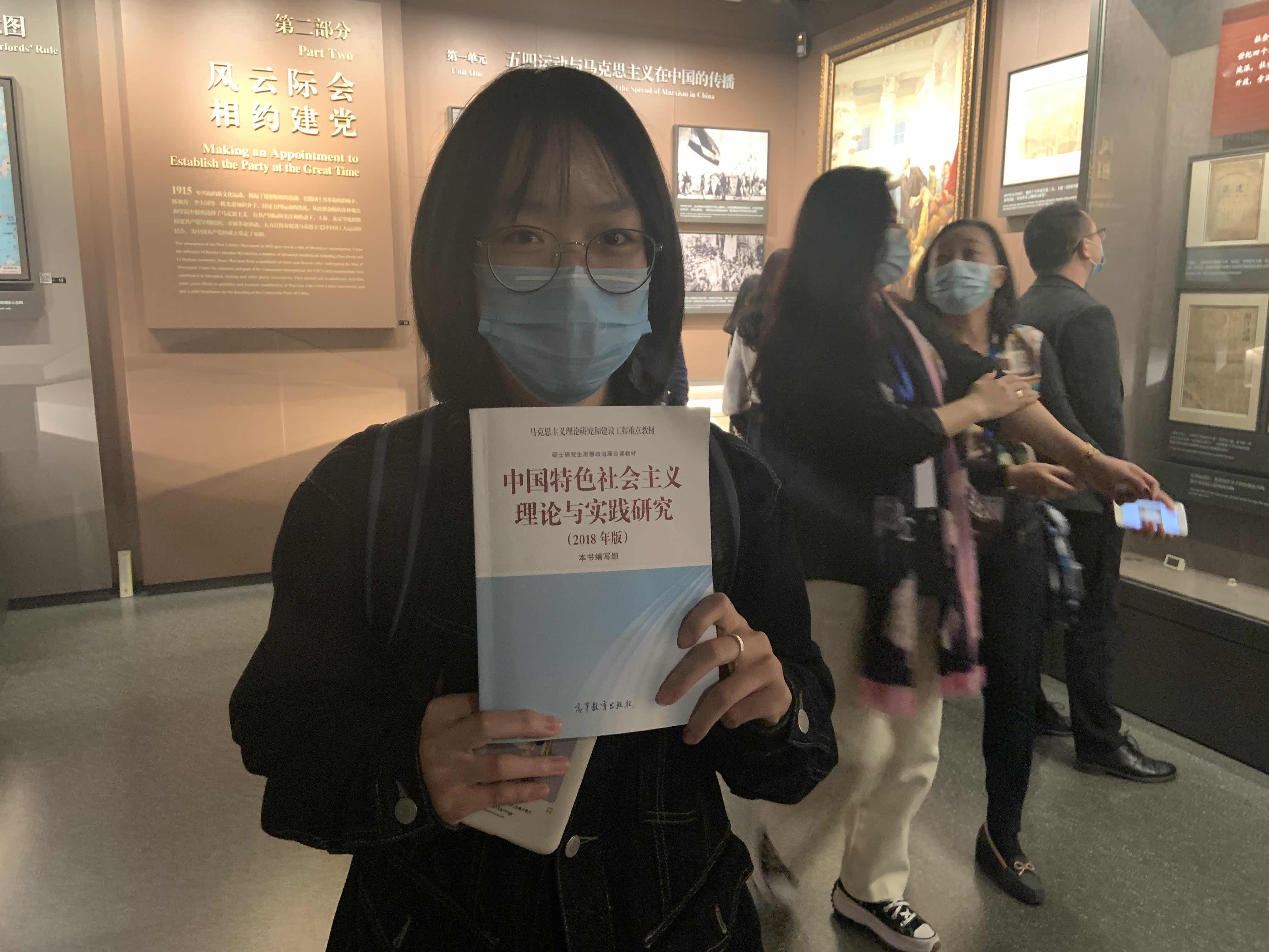 蓝盼盼手里拿着《中国特色社会主义理论与实践研究》。