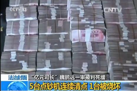 2014年,专案组在魏鹏远一处房屋中搜出大量现金。 央视新闻 截图