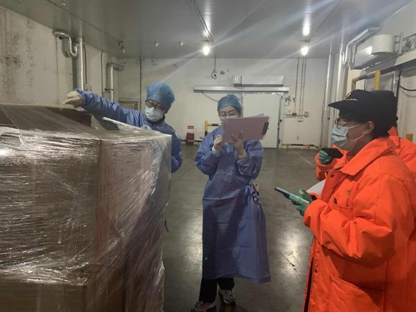 工作人员在货物仓门口进行严格检验